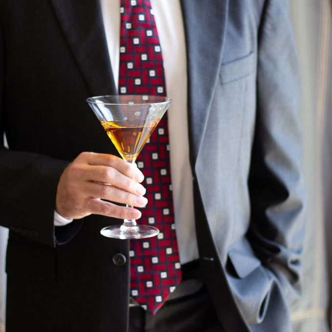 Stinger cocktail in hand of man in jacket and tie
