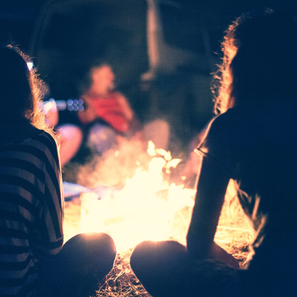 People sit at night round a bright bonfire