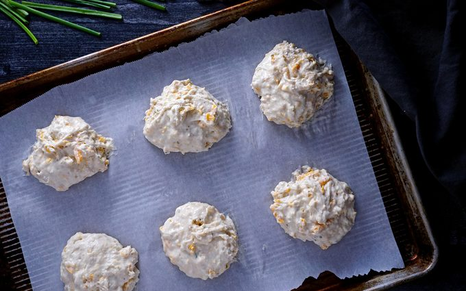 scooping heaping spoonfuls of cheddar bay biscuit dough onto lined baking sheet red lobster cheddar bay biscuits