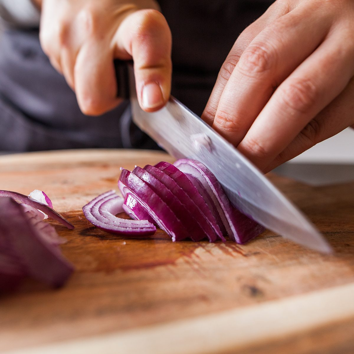 Cette photo représente une personne en train de couper des oignons rouges dans une cuisine.