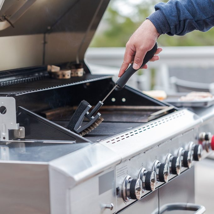 Cleaning outdoor gas grill before next grilling.