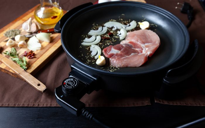 Electric pan with meat of pork on the table.