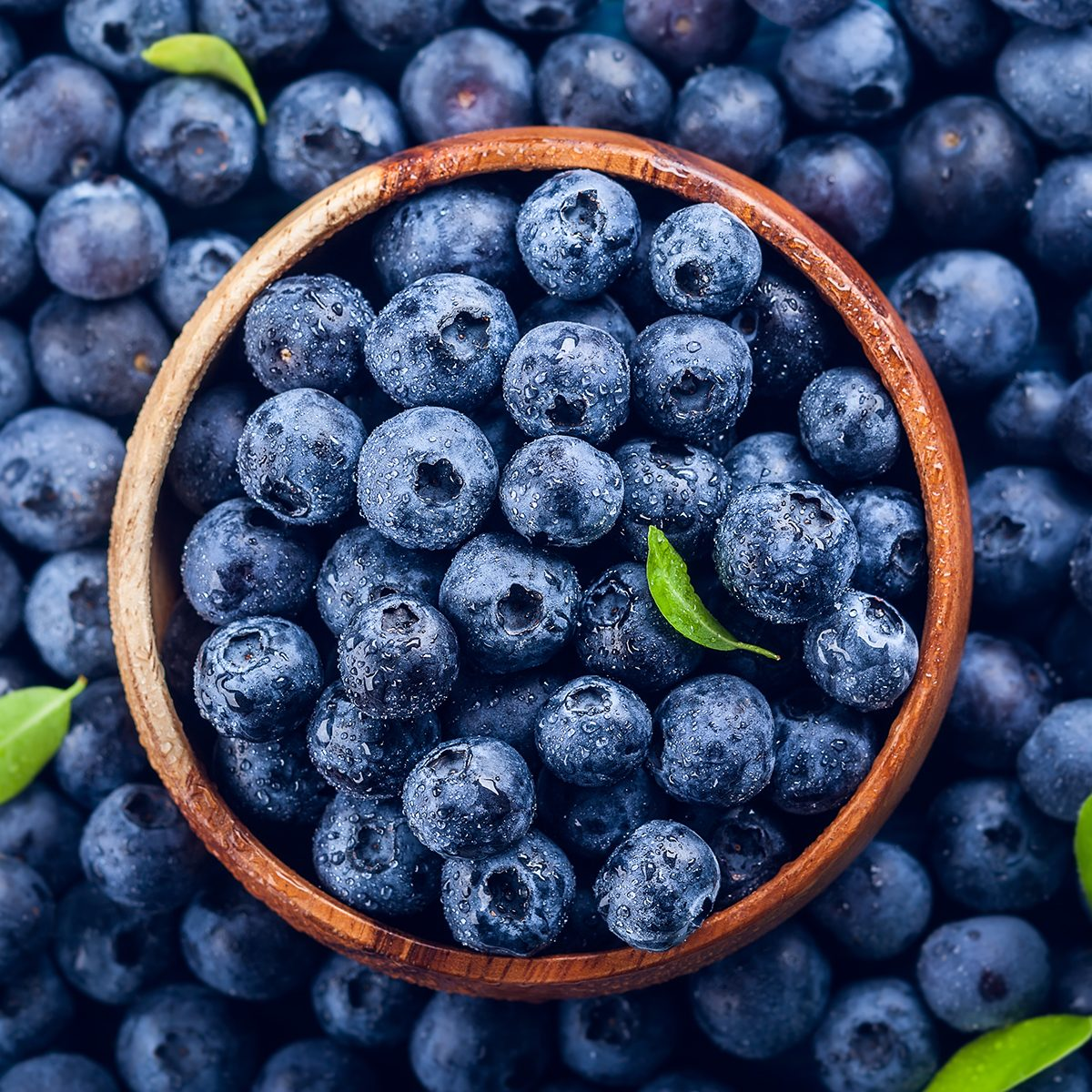 Fresh blueberry with drops of water in wooden bowl.