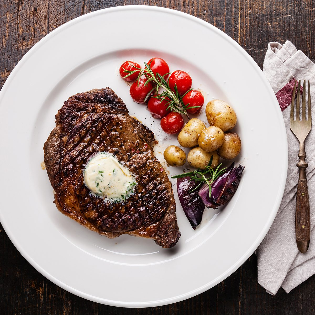 Grilled steak Ribeye with herb butter and baby potatoes on white plate on wooden background