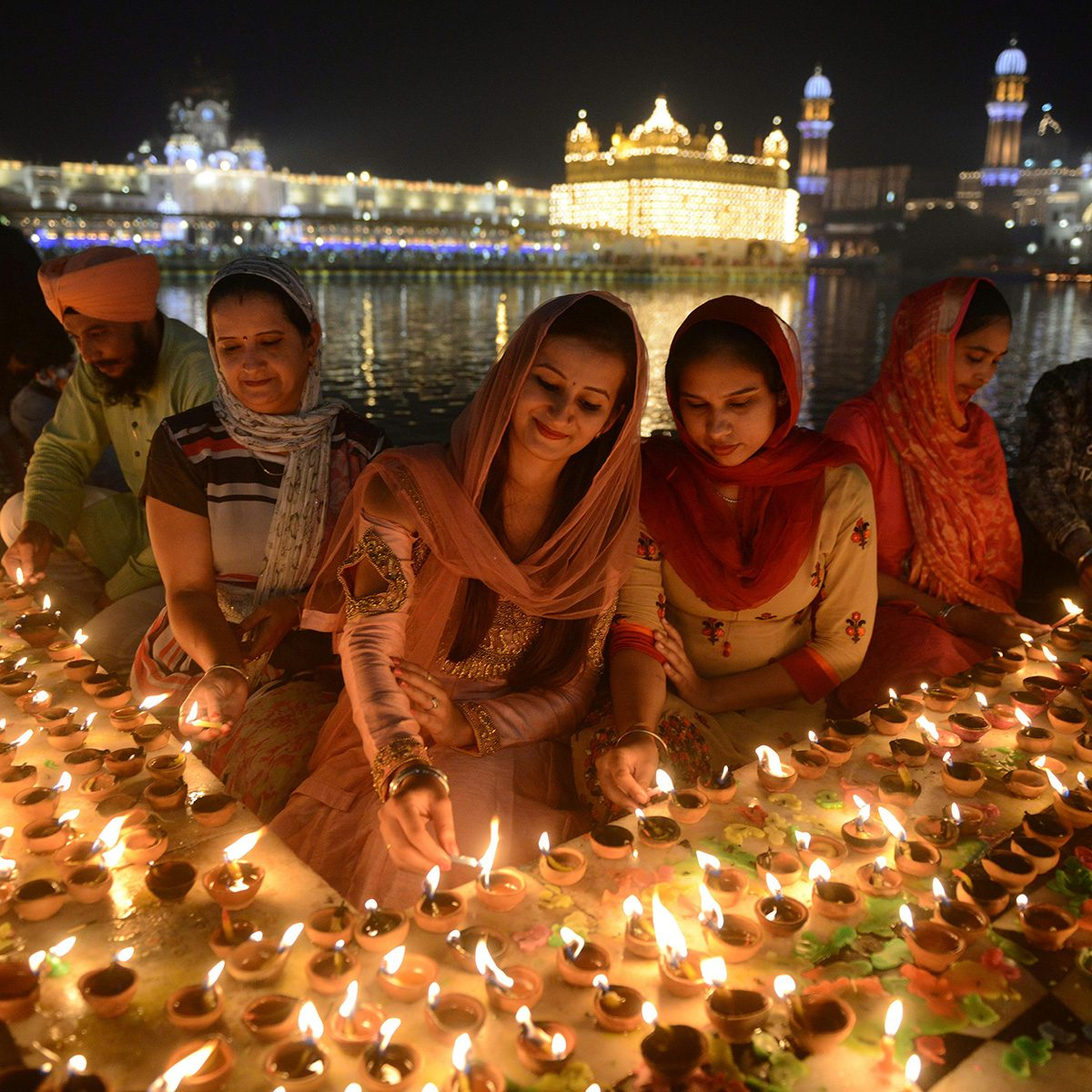TOPSHOT - Indian Sikh devotees light lights diyas (earthen lamps) during Bandi Chhor Divas or Diwali at the Golden Temple in Amritsar on November 7, 2018. - Sikhs celebrate 'Bandi Chhor Divas', also on the same day as the Hindu festival of Diwali, to mark the historic return of the sixth Guru, Guru Hargobind. (Photo by NARINDER NANU / AFP) (Photo credit should read NARINDER NANU/AFP via Getty Images)
