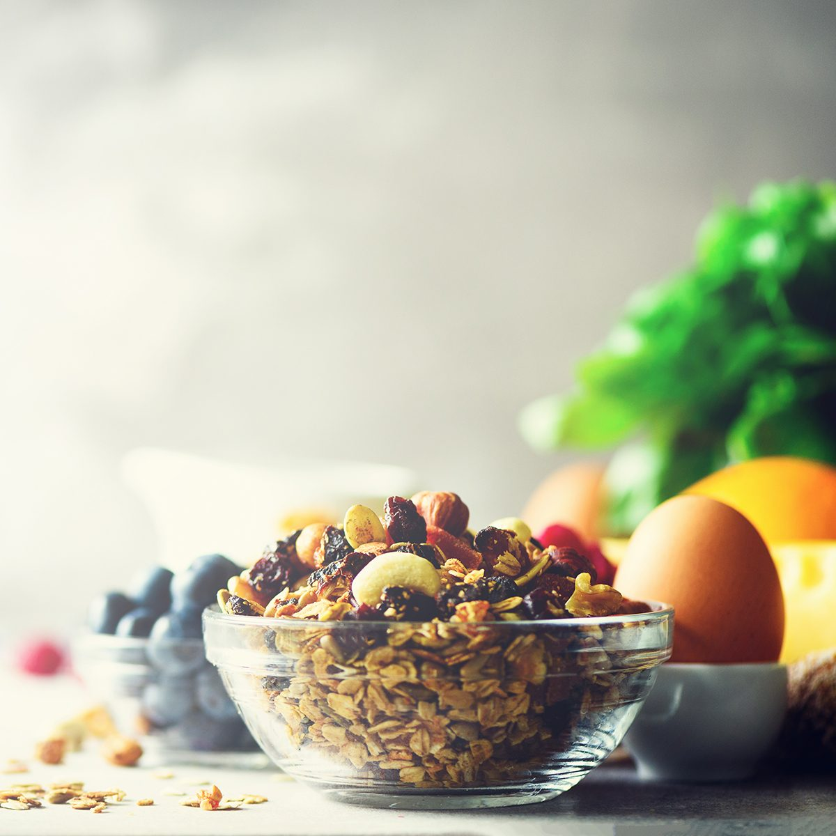 Organic ingredients for healthy lunch - berries, milk, egg, oatmeal on grey concrete background.