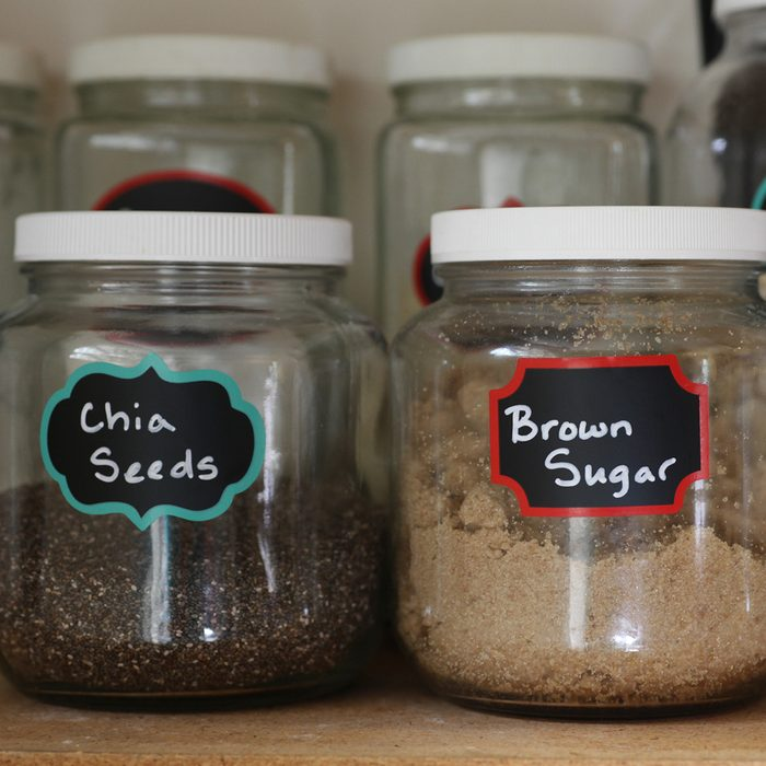 pantry glass jars filled with kitchen staples including oatmeal, brown sugar, and chia seeds on a shelf