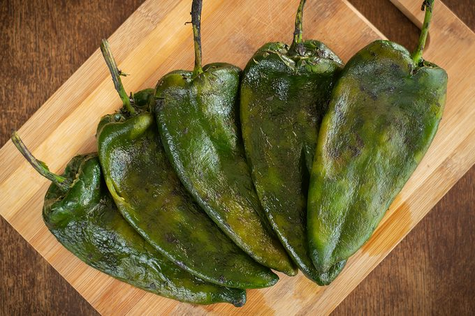 This image portrays 5 Poblano peppers roasted and deskinned, laid over a cutting board. This chili originates from Puebla, Mexico, and is typically used this way for recipes likes Chiles Rellenos (stuffed peppers) or Chiles en Nogada (Stuffed peppers drenched in walnut-based sauce). They are a common sight in Mexican households and a cultural staple in the country's culinary roots.