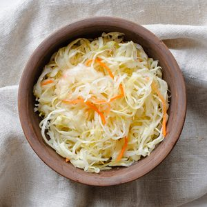 Top view of brown ceramic bowl of sauerkraut with chopped cabbage and carrot on grey towel sitting on white table surface; Shutterstock ID 1313830976; Job (TFH, TOH, RD, BNB, CWM, CM): TOH