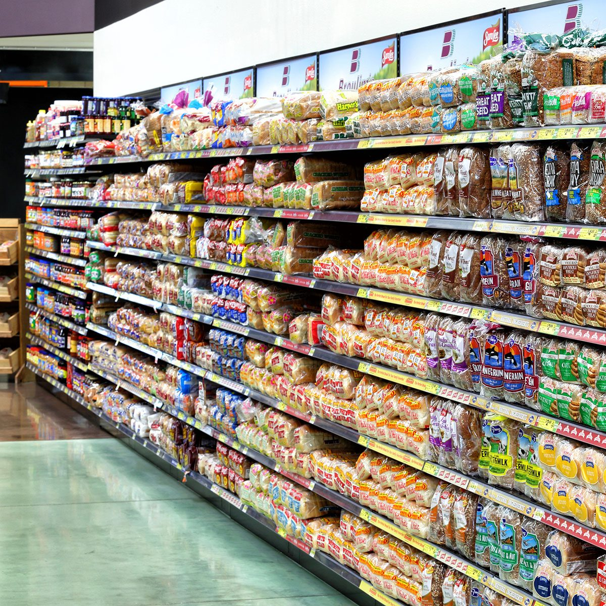 The interior of a modern grocery store showcasing the bread aisle with a variety of prepackaged breads available.