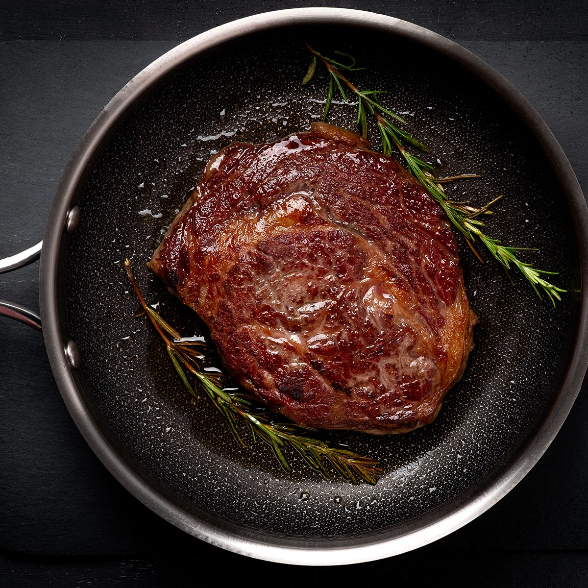 Grilled premium rib eye beef steak in the pan, cooking steak in the kitchen on a dark background