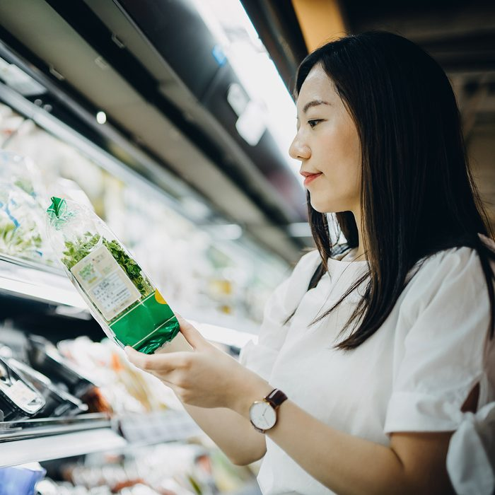 Young Asian woman with cart grocery shopping for fresh produce. She is shopping for fresh vegetables in a supermarket