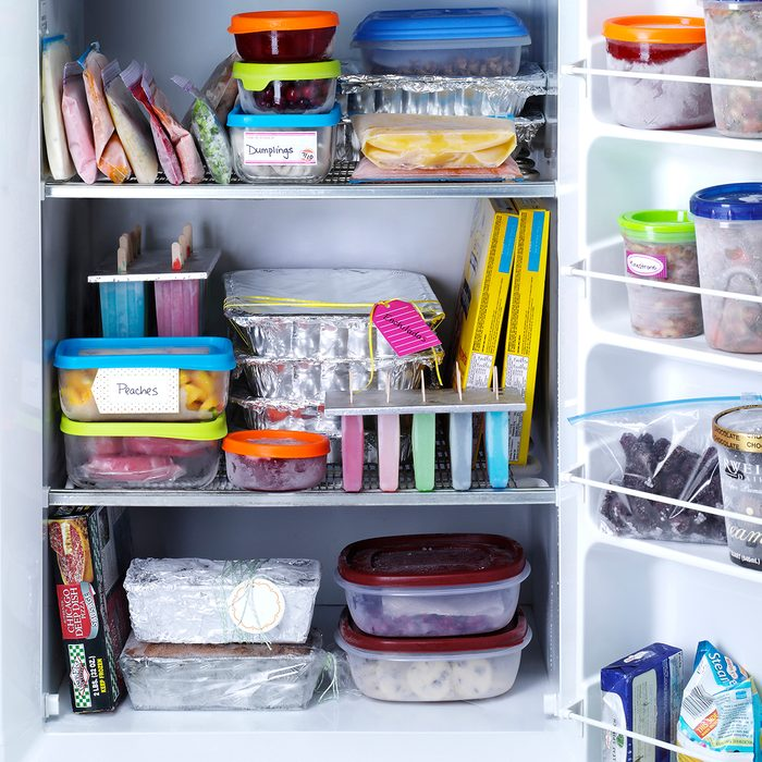An organized freezer with lots of labeled airtight containers and bags.