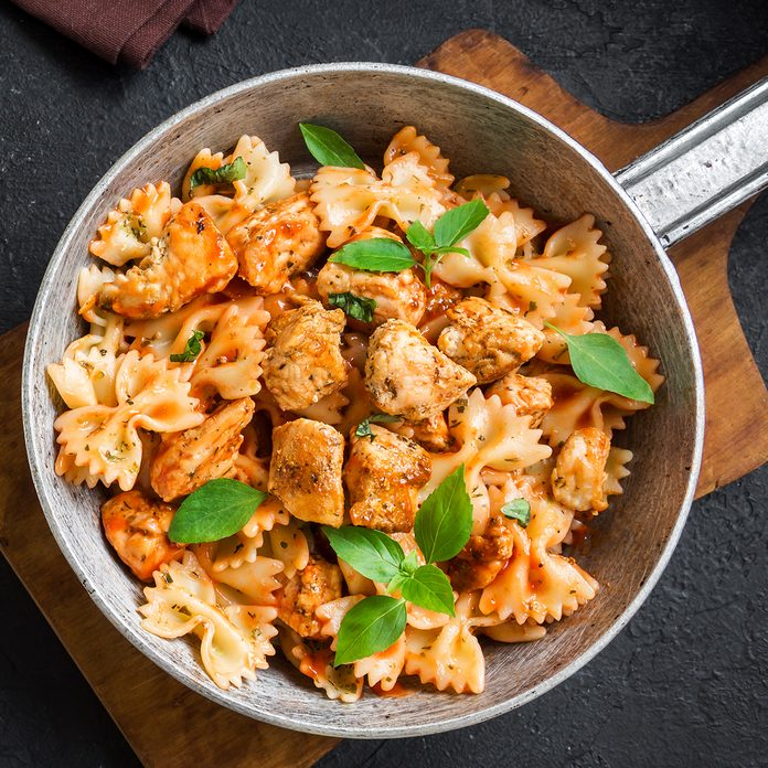 Farfalle pasta in tomato sauce with chicken, basil in pan. Chicken italian bow tie pasta over black background with copy space, homemade italian food.; Shutterstock ID 1241007715; Job (TFH, TOH, RD, BNB, CWM, CM): Taste of Home