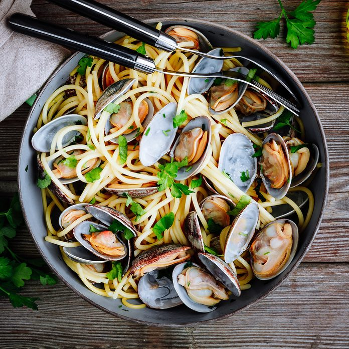 Traditional italian seafood pasta with clams Spaghetti alle Vongole in the pan on wooden background; Shutterstock ID 1319109386; Job (TFH, TOH, RD, BNB, CWM, CM): Taste of Home