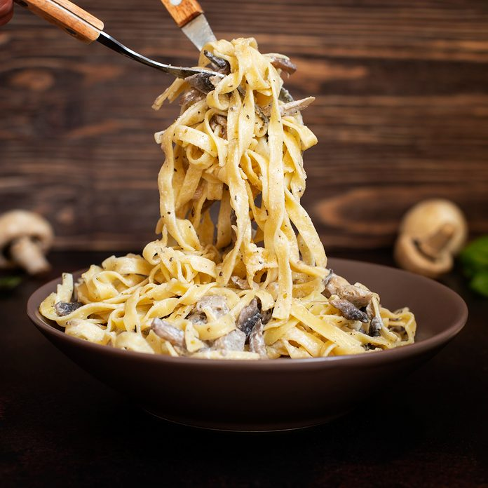 Homemade Italian fettuccine pasta with mushrooms and cream sauce (Fettuccine al Funghi Porcini). Traditional Italian cuisine. Served on a dark table with a rustic wooden background. Close-up; Shutterstock ID 1448882672; Job (TFH, TOH, RD, BNB, CWM, CM): Taste of Home