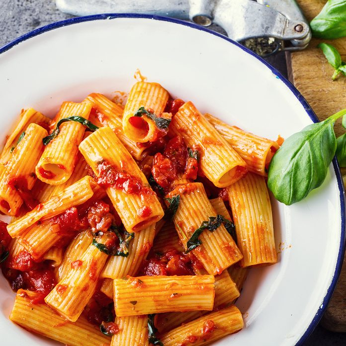 Pasta Rigatoni with tomato sauce basil leaves garlic and parmesan cheese.; Shutterstock ID 396666679; Job (TFH, TOH, RD, BNB, CWM, CM): Taste of Home