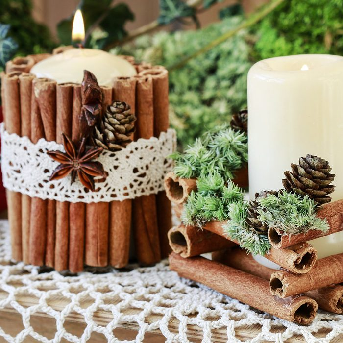 Candle decorated with cinnamon sticks
