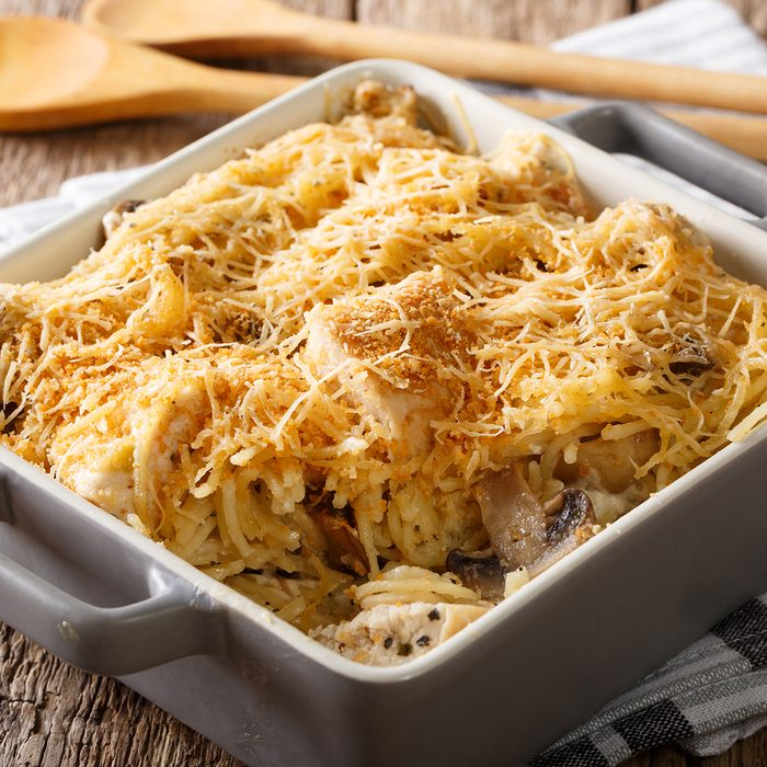 American tetrazzini with spaghetti, mushrooms, cheese, chicken close-up in a plate for baking on a table.