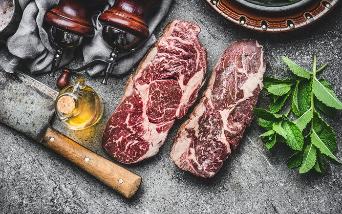 dry-aged steaks with meat cleaver