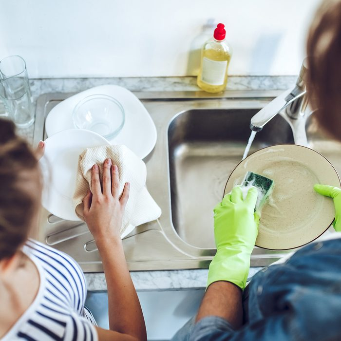 Top view of young happy couple is washing dishes while doing cleaning at home.