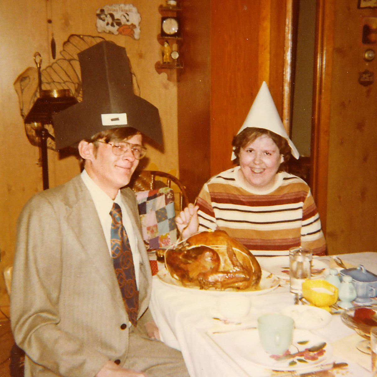 two older siblings wear funny pilgrim hats at the dinner table