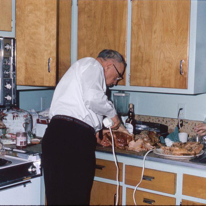man carves turkey with electric turkey carver