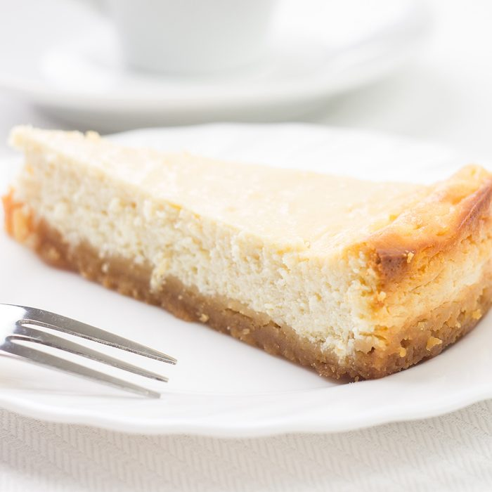 Piece of cheesecake on white plate with dessert fork. Menu recipe background