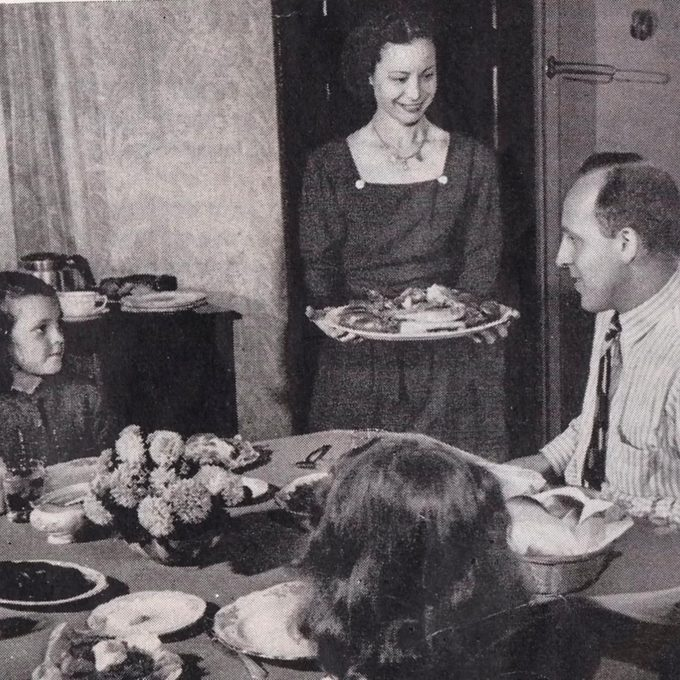 mother brings out plate of turkey to her family at the dinner table 1940s