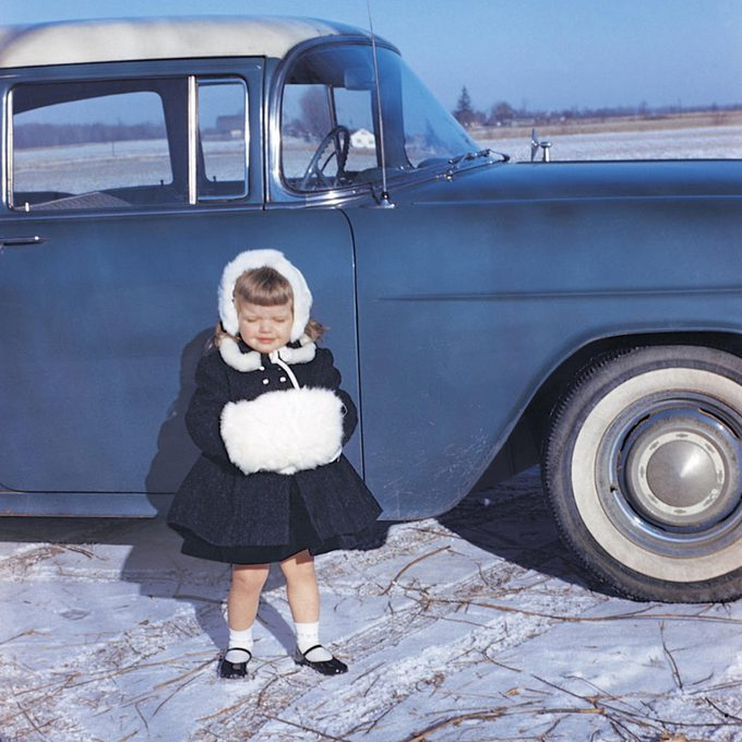 little girl stands in front of car dressed in a black winter outfit and hand warmers, 1960s