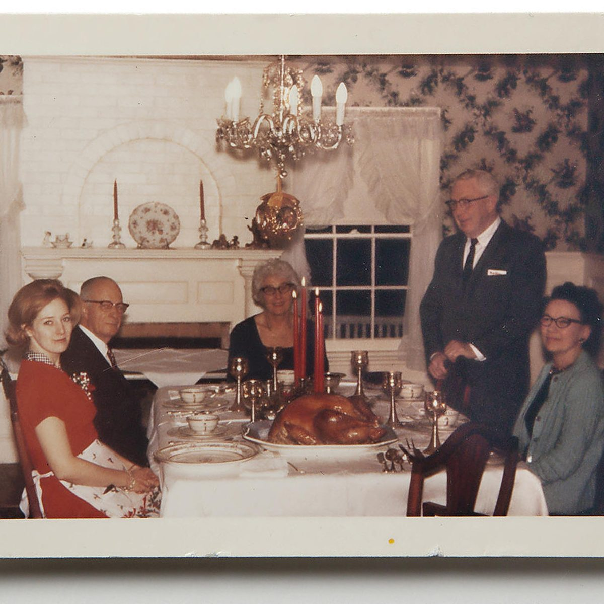 people around thanksgiving table with lit red candles
