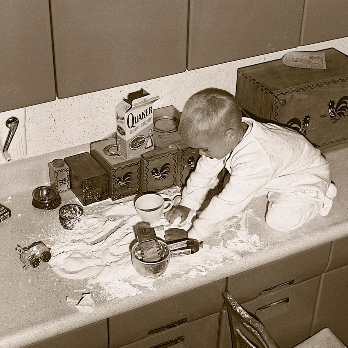 little boy making a mess with flour on the counter