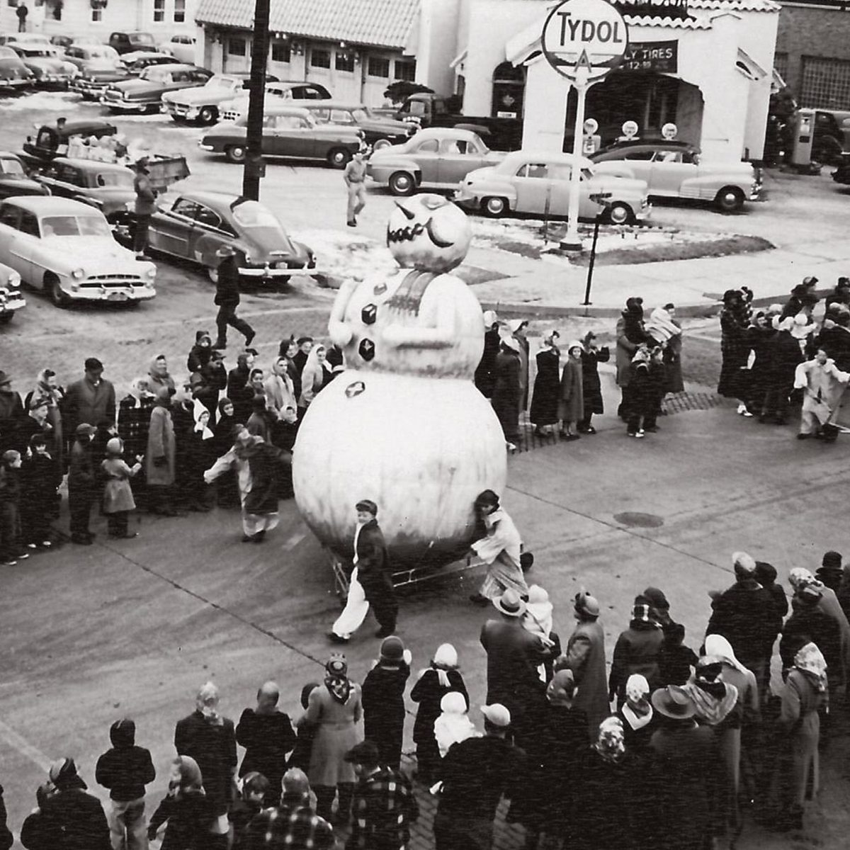 snowman float being wheeled down street during thanksgiving parade in Sheboygan Wi 1950s
