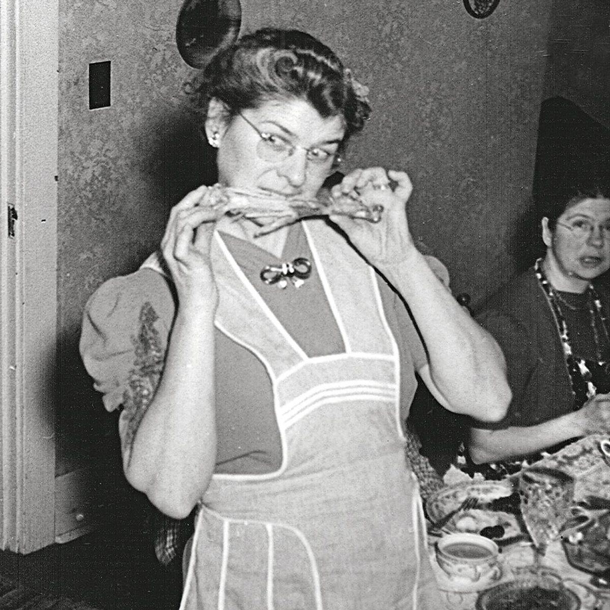 1930s woman jokingly biting a turkey leg while family looks on in confusion