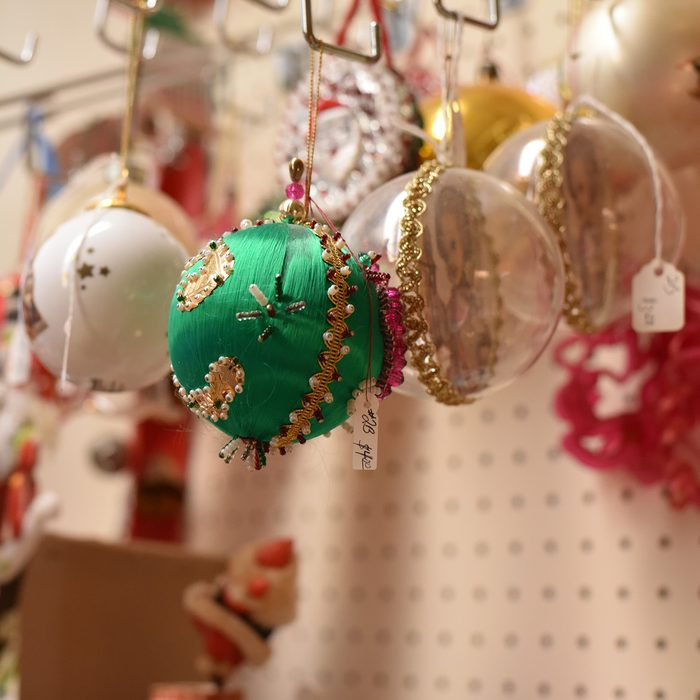Colorful antique vintage Christmas ornaments displayed for sale on a pegboard in a thrift store.