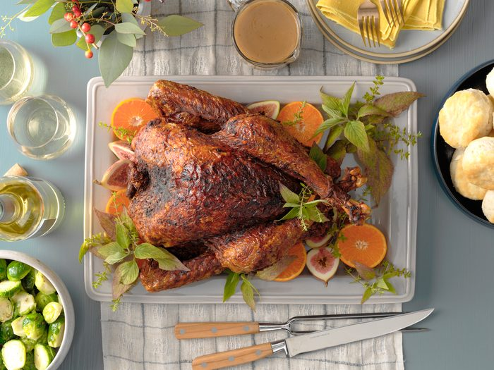Deep-fried turkey on table with oranges and herbs.