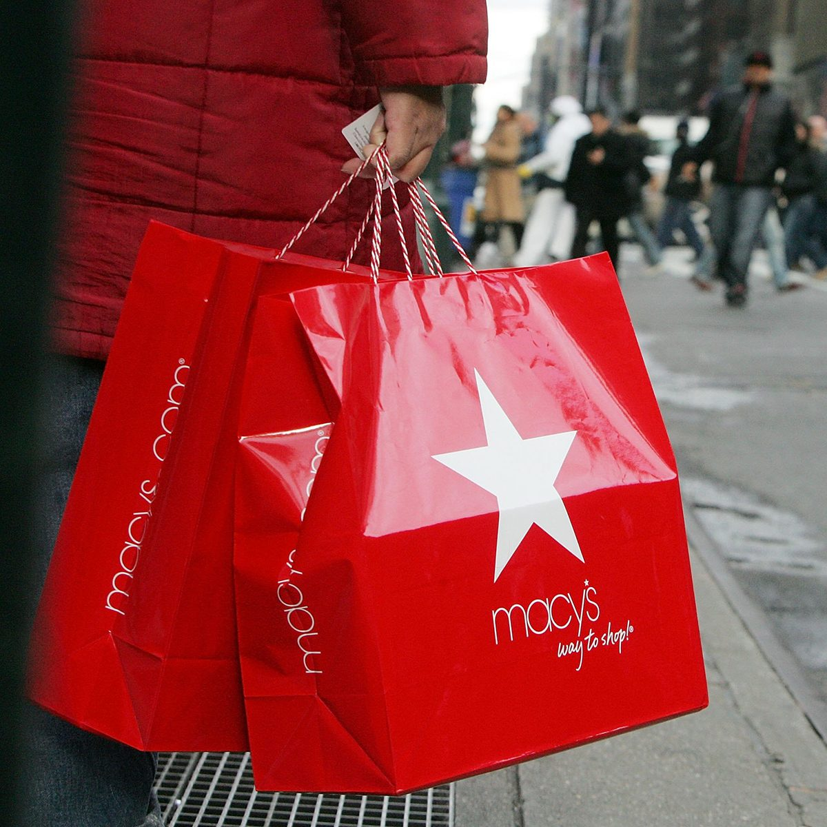 NEW YORK - DECEMBER 27: A post-Christmas shopper holds Macy's bags as other shoppers cross Seventh Avenue December 27, 2006 in New York City. Retailers are hoping that after-Christmas shoppers will help them regroup after a somewhat disappointing holiday shopping season thus far. (Photo by Mario Tama/Getty Images)