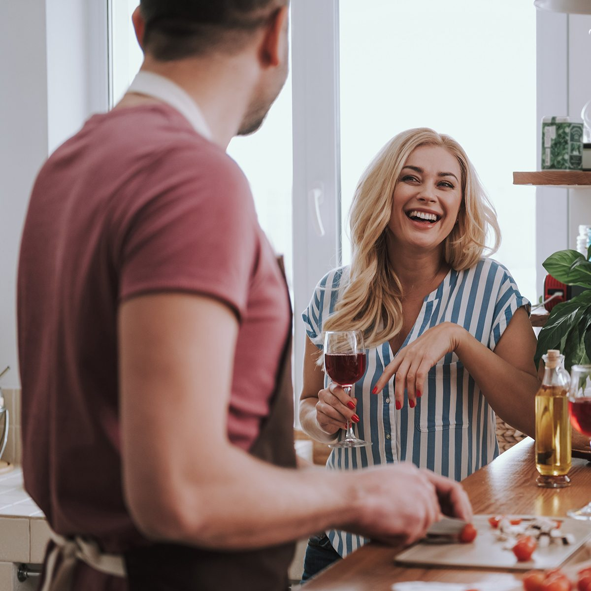 Man cooking while woman drinking wine watches