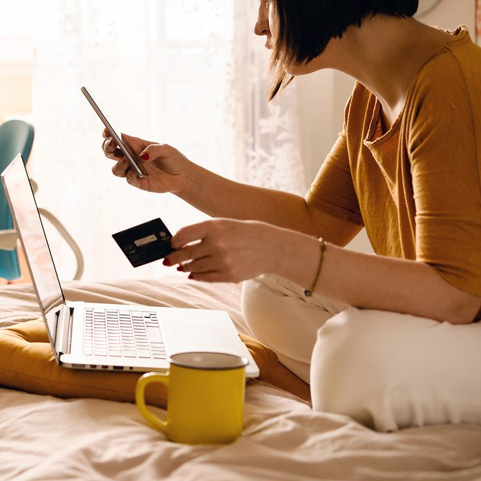 A middle-aged woman in white jeans and a yellow sweater sitting on the bed in a yoga pose in front of a laptop and a cup of coffee. Remote work at home. Online shopping in quarantine period