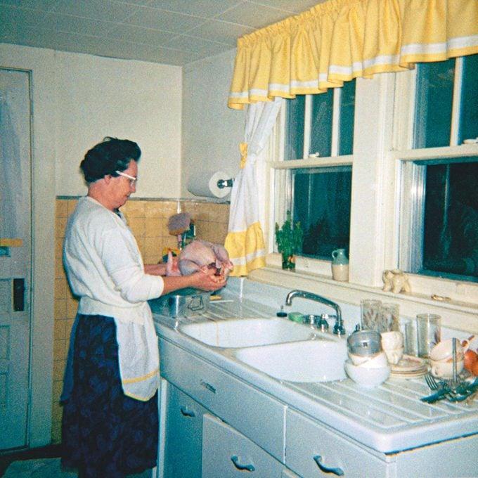 older woman holding raw turkey above sink 1960s
