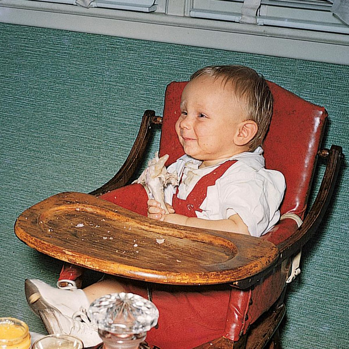 Infant boy smiles as he eats a turkey leg in his high chair on his first thanksgiving