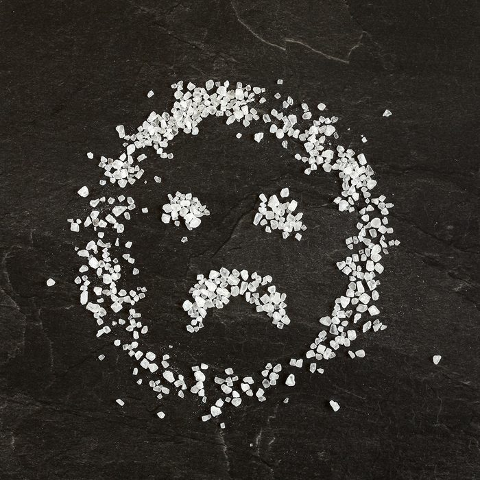 Sad face emoticon made from salt crystals
