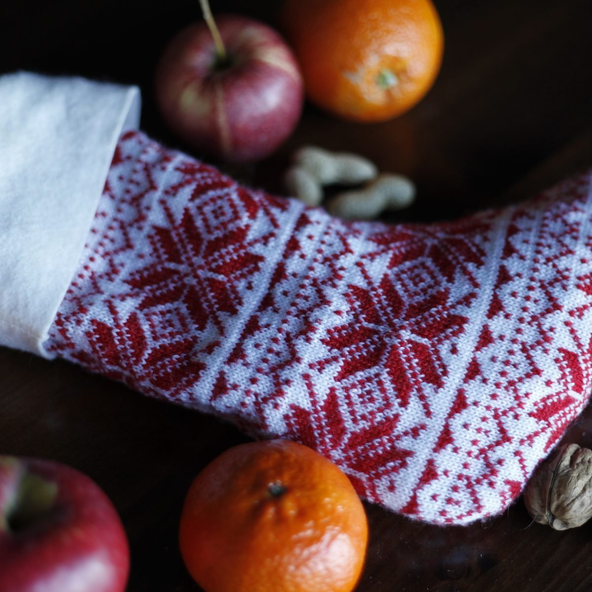 Knitted red and white Santa stocking with nuts, apples and oranges