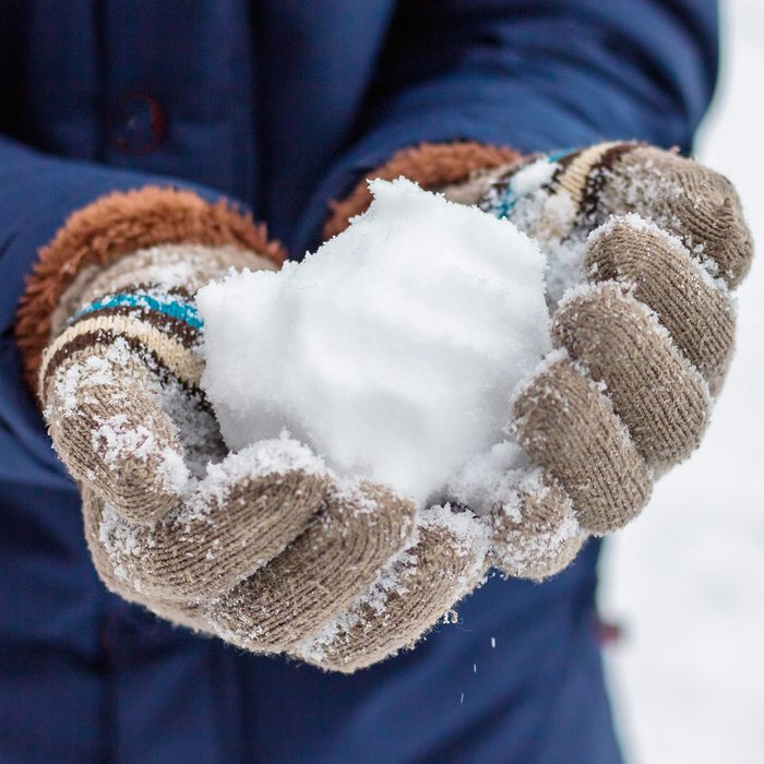 A girl in mittens holds a snowball. Playing snowballs on a clear winter day