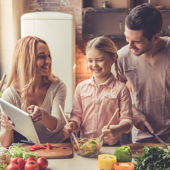 Cute little girl and her beautiful parents are using digital tablet and smiling while cooking in kitchen at home