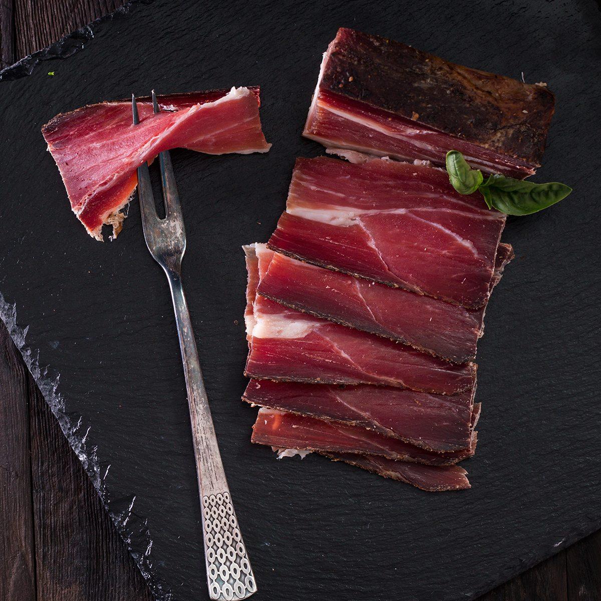 italian Speck, delicious ham on vintage background