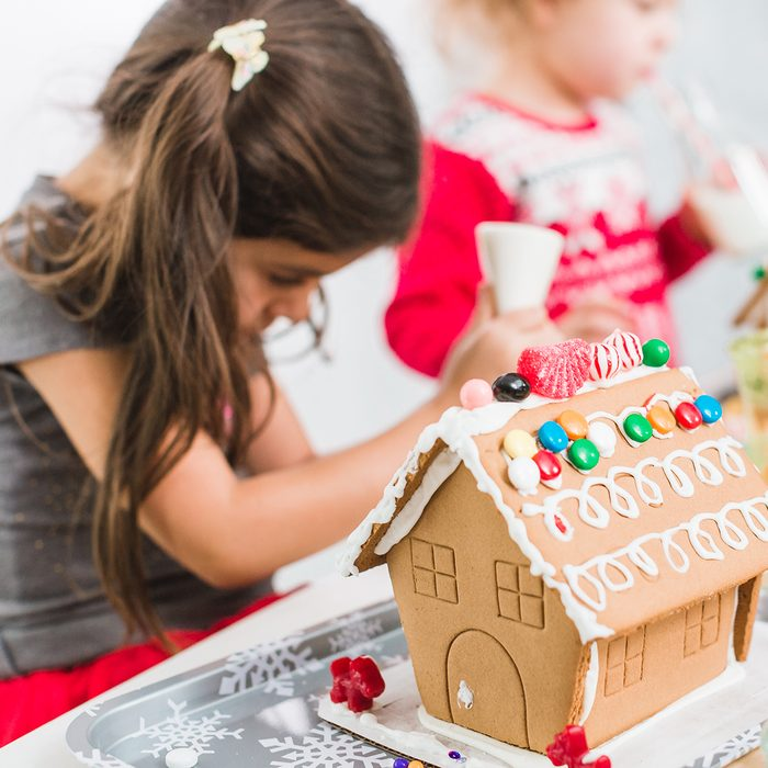 Kids decorating small gingerbread houses at the Christmas craft party.
