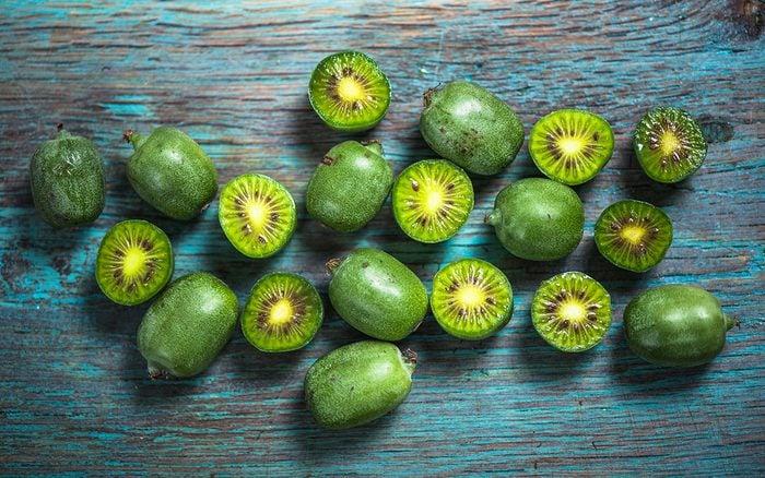 Kiwi berries on vibrant wooden board