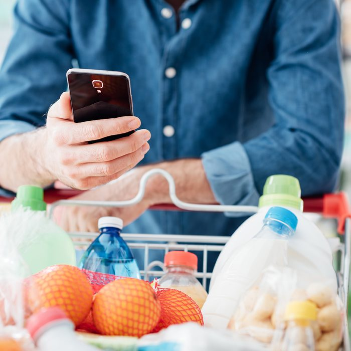 Man shopping at the supermarket, he is leaning in the shopping cart and connecting with his mobile phone; Shutterstock ID 617768495; Job (TFH, TOH, RD, BNB, CWM, CM): TOH