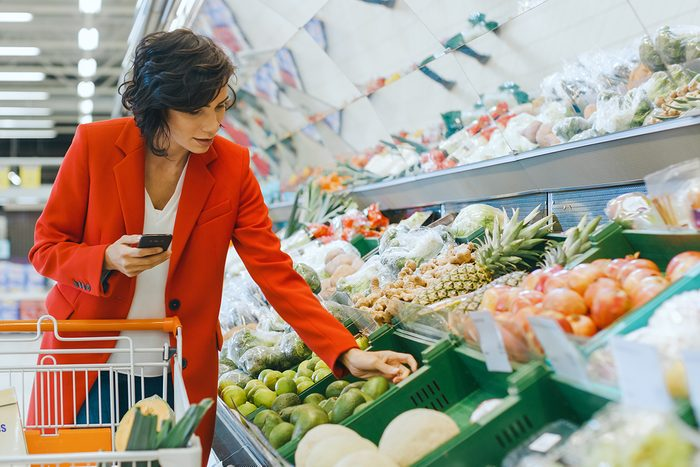 At the Supermarket: Beautiful Young Woman Walks Through Fresh Produce Section, Chooses Vegetables and Places them in Her Shopping Cart. Customer Uses Smartphone while Shopping for Fruits; Shutterstock ID 1275256033; Job (TFH, TOH, RD, BNB, CWM, CM): Taste of Home